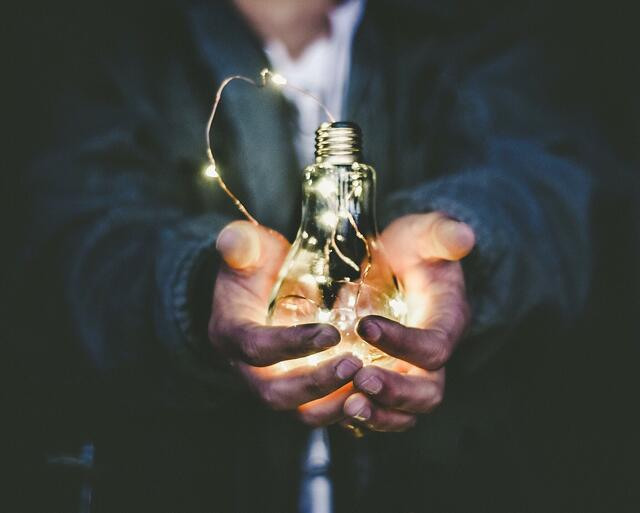 lit_lightbulb_between_hands_by_riccardo_annandale.jpg