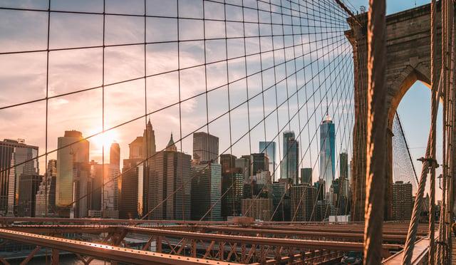 Brooklyn-bridge-with-sun-through-NYC-skyline