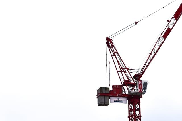 red-construction-crane-against-white-sky